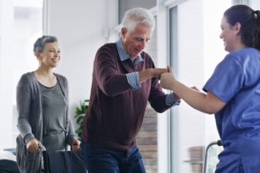 Senior man getting up to walk after surgery with nurse supervision