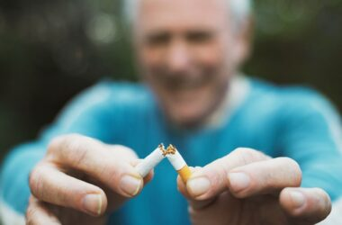 Senior man quitting smoking breaks his last cigarette with a smile