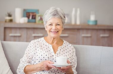 Smiling senior woman drinking lukewarm coffee to reduce her risk of esophageal cancer