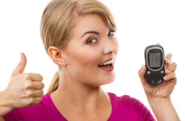 Woman holding blood sugar monitor giving thumbs up after taking cinnamon to avoid prediabetes