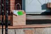 Contactless food delivery brown bag on the porch of a house for coronavirus pandemic safety