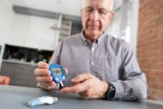 Senior man with prediabetes is taking his blood sugar at home