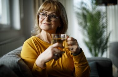 Smiling senior woman drinking green tea to ward of heart attack and stroke