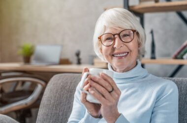 Smiling senior woman holds a cup of heart failure fighting coffee