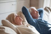 Smiling stress free senior couple napping on sofa after taking probiotics