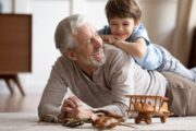 Happy grandfather playing with grandson on the floor thanks to Terpacanol relieving overworked joint pain