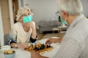 Senior couple in masks with no cognitive decline playing chess