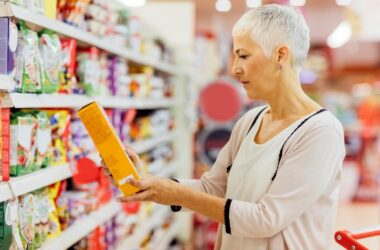 Senior woman reads food label looking for immune system damaging additive