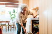 Smiling senior woman fights mobility issues by loading dishwasher