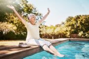 Lady sitting in sunlight poolside reaping health benefits including lower COVID-19 death risk