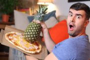 Man holds whole pineapple on pizza