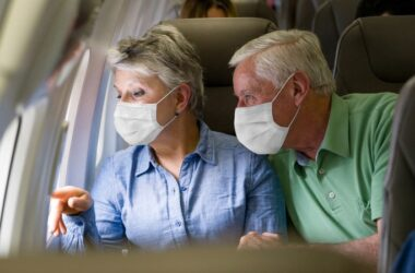 Senior couple travel by plane wearing facemasks