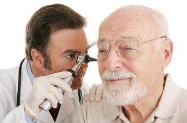 Senior man in glasses getting ears checked by doctor to help lower dementia risk