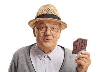Senior man holds a flavanol rich chocolate bar with a bite out of it