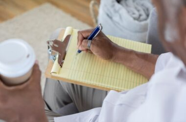 Senior man writing notes on a yellow pad of paper to help his memory