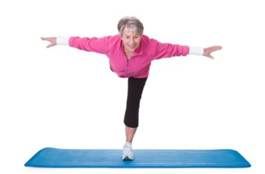 Senior woman with strong leg muscles balancing on one leg