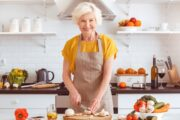 Senior woman smiling in kitchen as she cuts cancer fighting mushrooms
