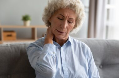 Unhappy senior woman suffering from chronic pain massaging neck muscles