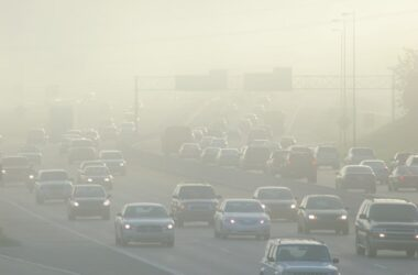 Cars on highway driving through thick air pollution smog
