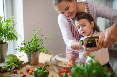 Girl with grandmother add extra virgin olive oil to salad to help protect against kidney disease