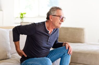Senior man in pain sits on couch with hand on back