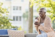 Senior woman relaxing on patio with iced coffee