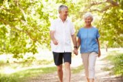 Smiling senior couple walking on a path for exercise to extend life