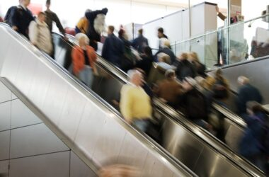 Crowd in blurred motion on escalator to illustrate post pandemic stress