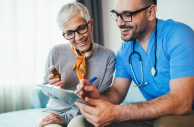 Doctor reviews meds with smiling senior woman