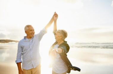 Senior couple on beach dance in sunshine without wearing sunscreen