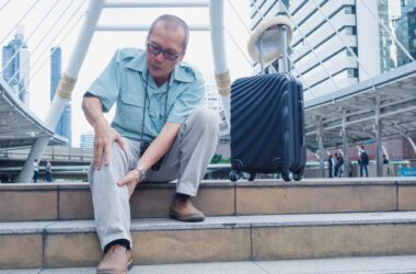 Senior traveler with suitcase sitting with blood clot triggered leg pain