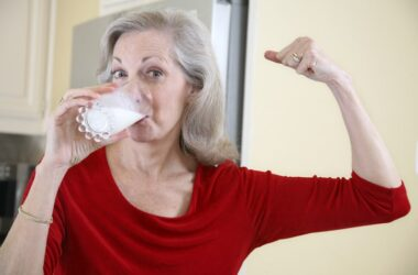 Senior woman drinking milk to reduce heart risk and showing arm muscle