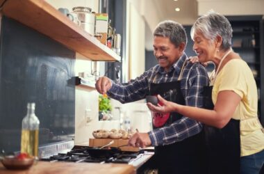 Smiling senior couple adding salt to the dish they are cooking