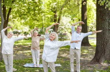 Smiling seniors practicing tai chi in the park to lose belly fat