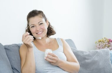 Woman sitting on sofa smiling and eating yogurt to reduce breast cancer risk