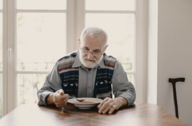 Senior man battling loneliness eats soup alone in an empty apartment