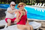 Smiling senior applies sunscreen to wife poolside