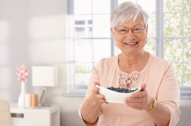 Smiling senior lady holds a bowl of brain boosting blueberries