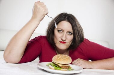 Unhappy woman about to stab fake meat burger with a fork
