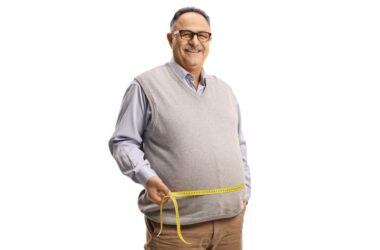 Mature man measuring waist to check belly fat loss