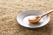 Pouring sesame oil into a small ceramic dish sitting on sesame seeds
