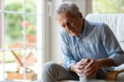 Senior man with pain in his knees grasps left knee and grimaces