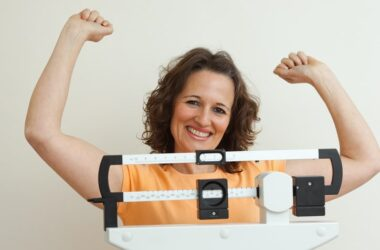 After losing weight happy woman stands on scale in victory