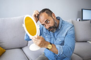 Mature man concerned by hair loss and going bald looks at head in mirror