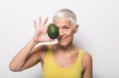 Mature woman holding body fat fighting avocado over her right eye
