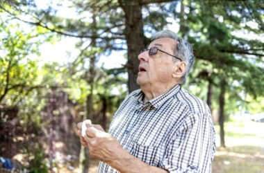 Older man with autumn allergies outside sneezing