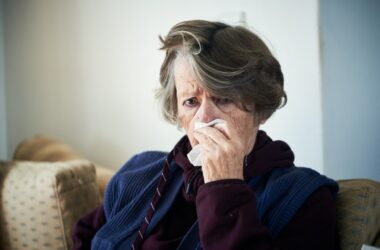 Senior woman with a cold dabs at the snot forming in her nose