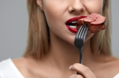 Close up of woman biting into a piece of CoQ10 rich meat