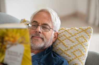 Senior man reading book after having vision checked and corrected