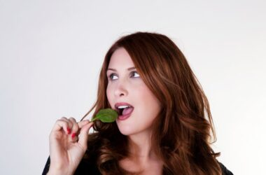 Woman about to bite into a spinach leaf to lower colon cancer risk